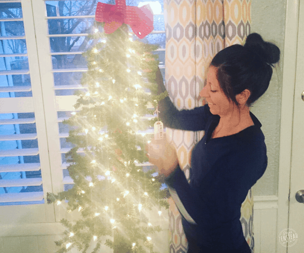 woman decorating lighted tree