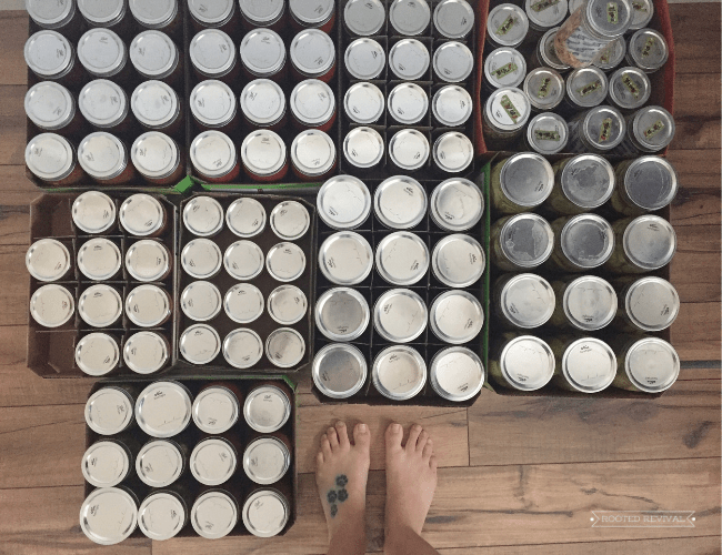 an overhead picture of a person's feet next to numerous canned jars